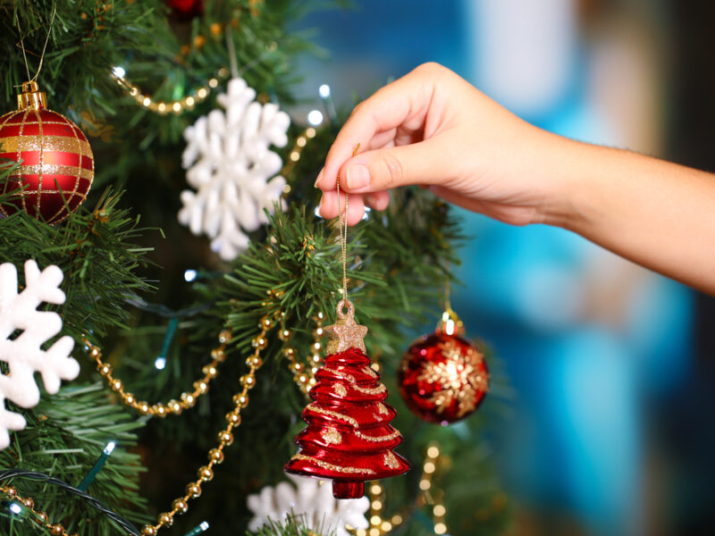 A woman's hand places a shiny red Christmas tree shaped ornament upon a sparkling tree.