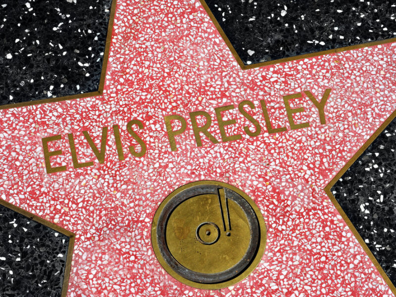 A close up of Elvis' Hollywood Star of Fame, a red star on black tile with his name spelled out across it..