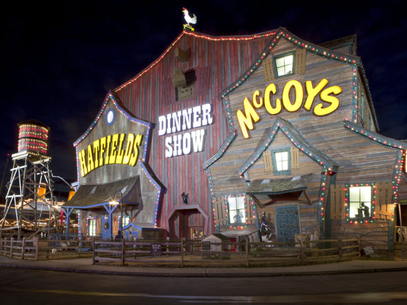 The entrance to the Hatfields and McCoys Dinner Feud in Pigeon Forge. The building looks like an old barn with lights strung across it.