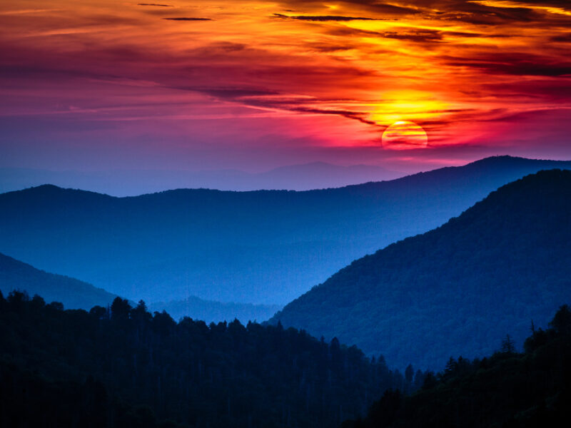 A orange and lilac sunset descends over silhouetted trees in the Smoky Mountains.