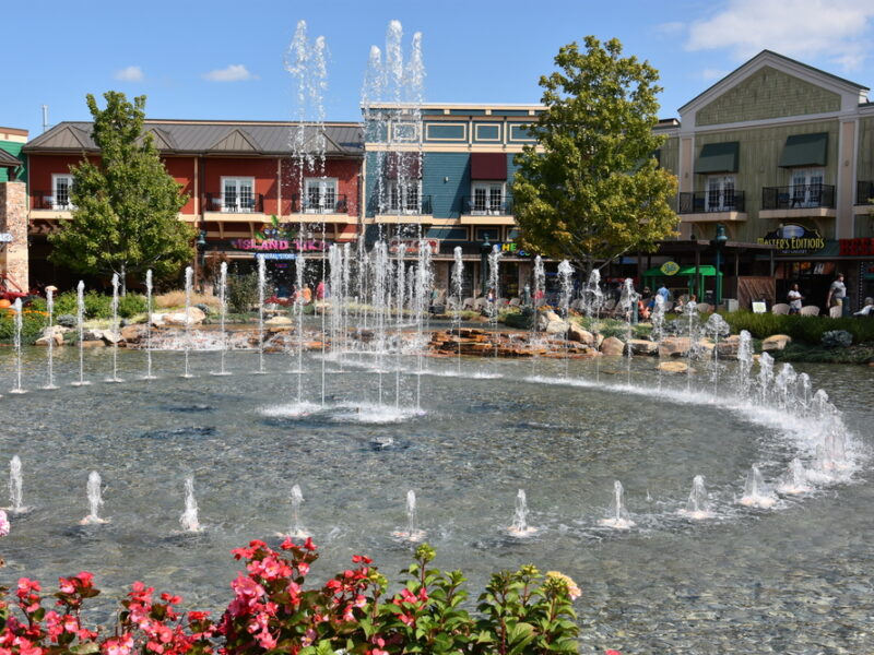 A view of the fountain show at The Island, Pigeon Forge. Spurts of water shoot up from sparkling water in a circle pattern. A line of charming shops cross the background.