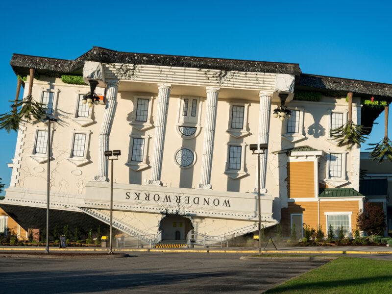 "An upside down building with Greek style column reads ""Wonderworks.""s."