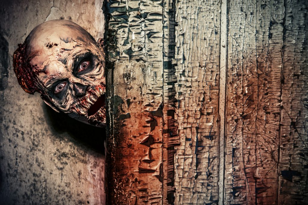 Photo of a scary zombie peeking around a corner.