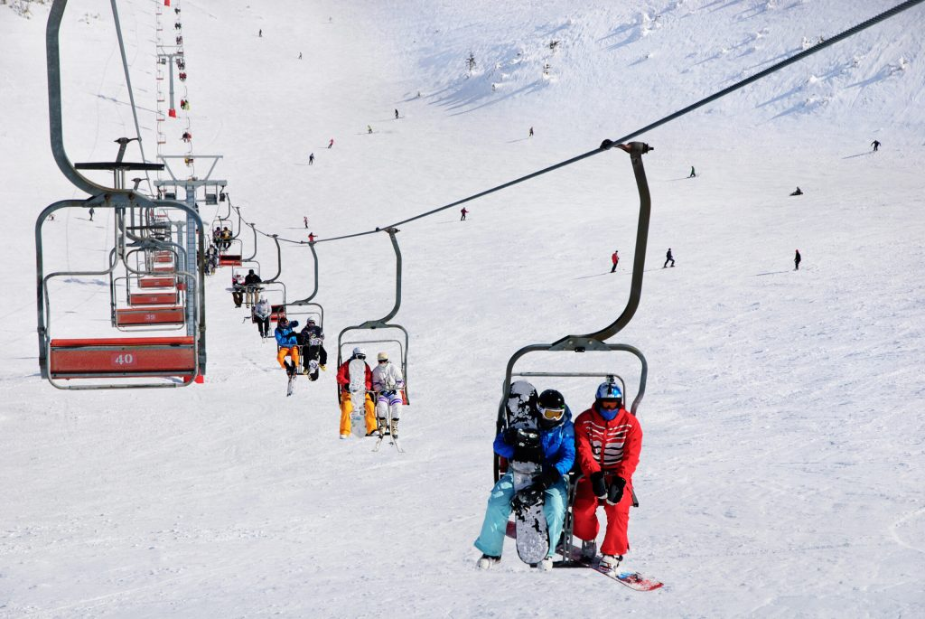Photo of several people riding a ski lift.