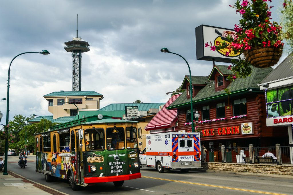 Photo of the Gatlinburg Trolley with the Gatlinburg Space Needle seen in the background. One of the fun free things to do in Gatlinburg.
