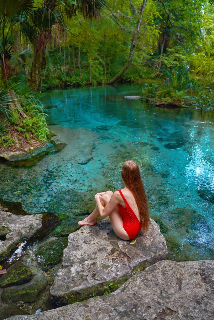 Photo of young woman in a red swimsuit sitting on a rock looking at the spring water in Florida.