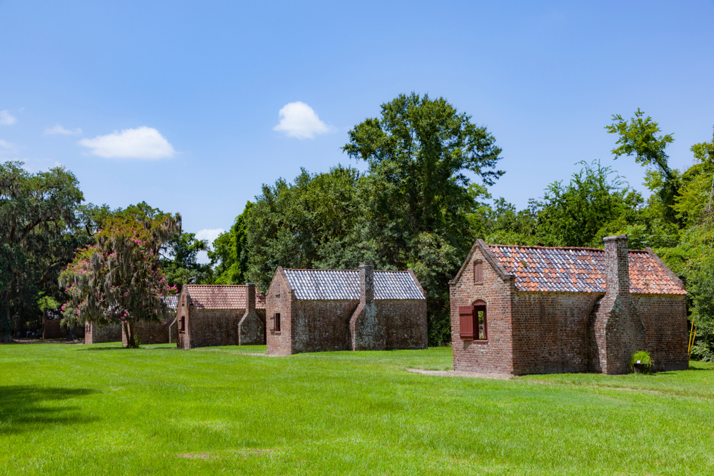 The slave quarters at the Boone Hall Plantation on a sunny day on a grassy field one of the best south carolina road trips