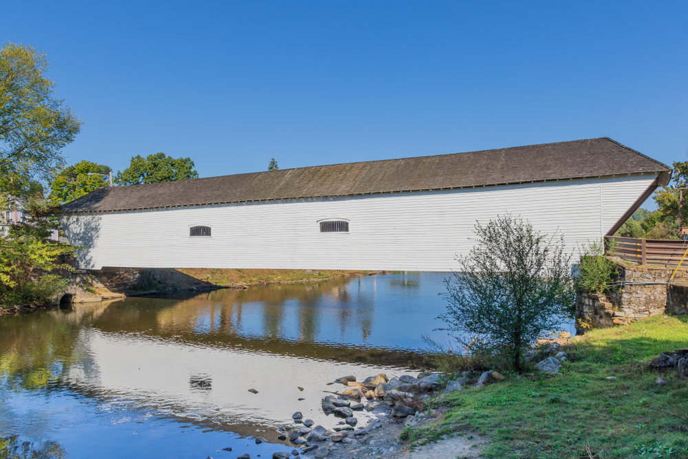 A white covered bridge in Tennessee that crosses a wide creek