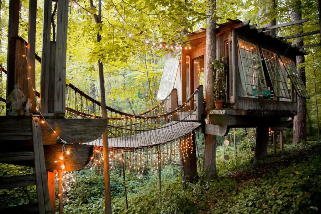 treehosue with a suspended rope bridge
