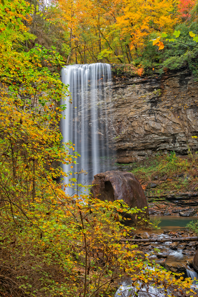 A tall waterfall surrounded by fall foliage at a state Park on a Georgia Fall Foliage road trip
