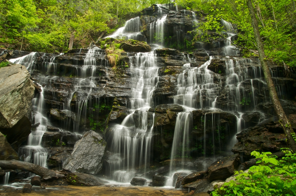 Issaqueena Falls which is a massive cascading waterfall in South Carolina surrounded by greenery one of the best South Carolina road trips
