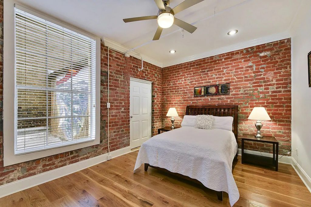 Photo of a condo on Union Street that is an Airbnb in New Orleans. Beautiful bedroom with historic brick wall.