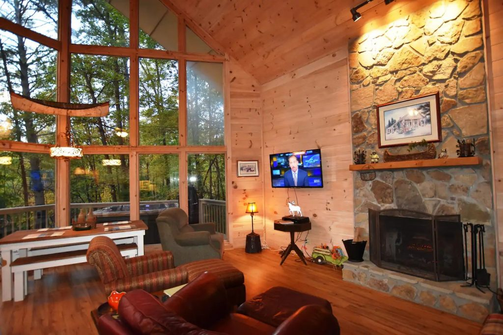 cozy living room with floor to ceiling windows and tree view