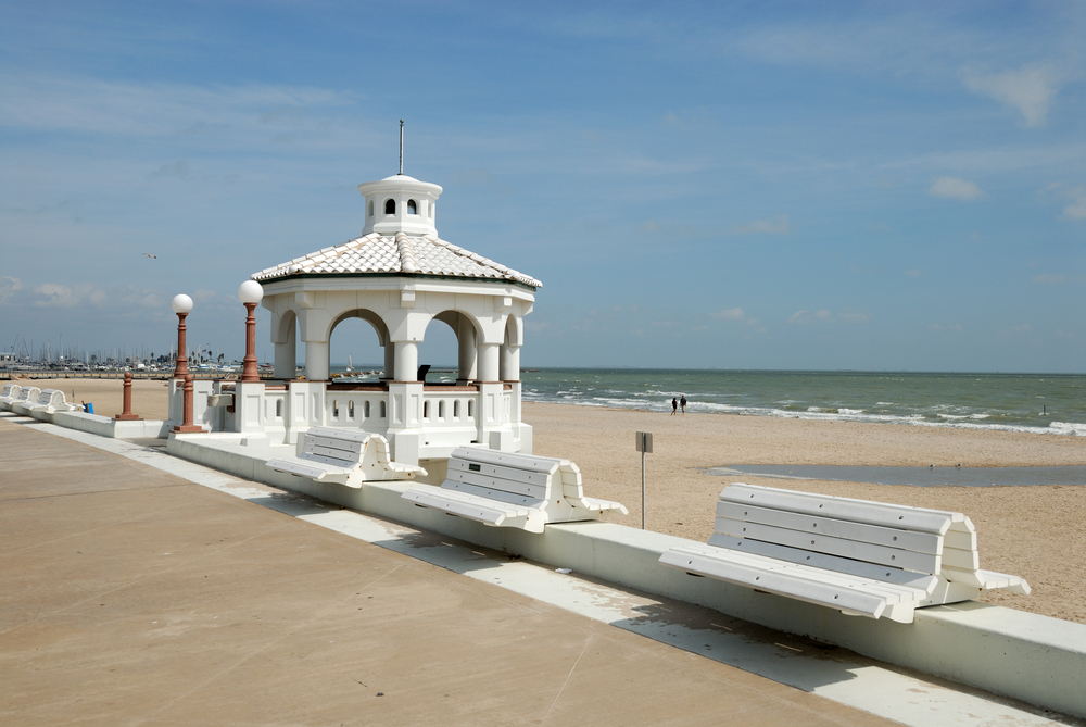 A photo of white benches on Corpus Christi Beach. One of the prettiest beaches in Texas.