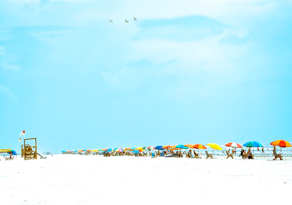 A photo of a row of colorful umbrellas along Stewart Beach. One of the prettiest beach in Texas.