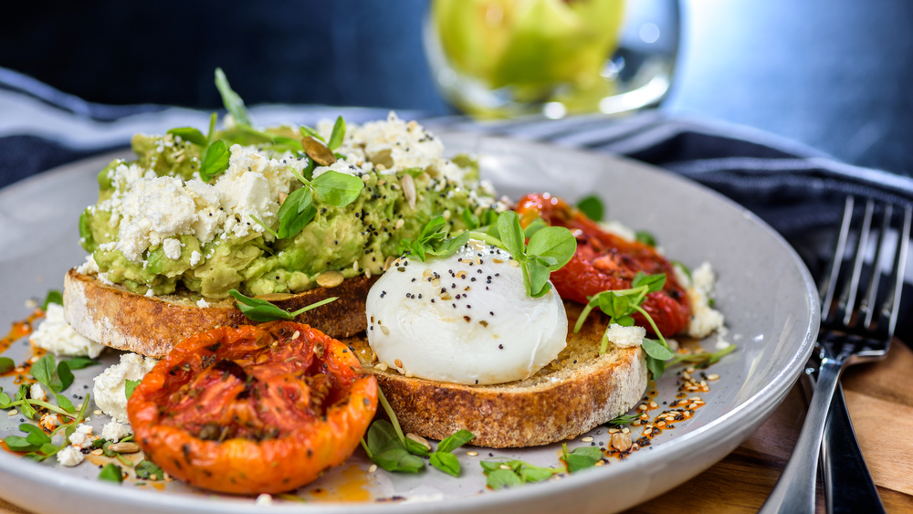 Photo of avocado toast topped with poached eggs, a tasty option for the best breakfast in Savannah