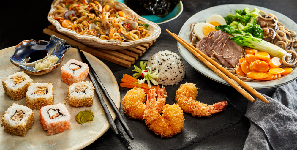 Photo of a spread of sushi, noodles, and Thai stir fry which are all delicious dishes to order at Asian restaurants in Savannah.