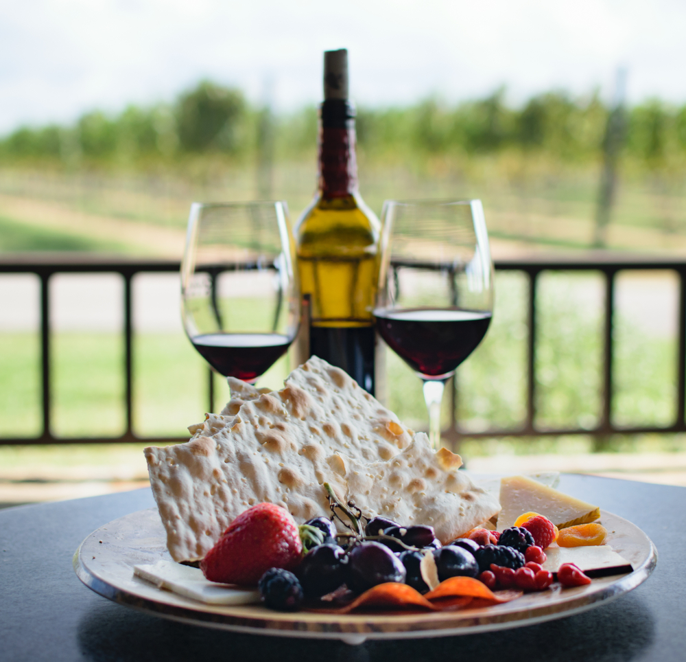 Photo of wine glasses and a plate of cheese and crackers at a winery in Fredericksburg, one of the best weekend getaways in Texas.