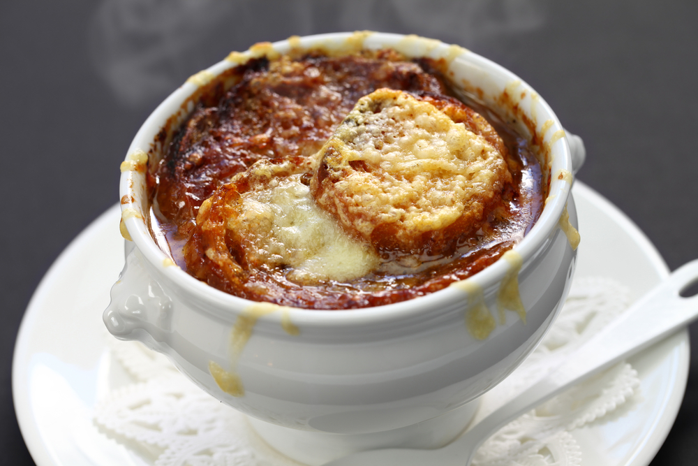 A bowl of French onion soup in a white bowl