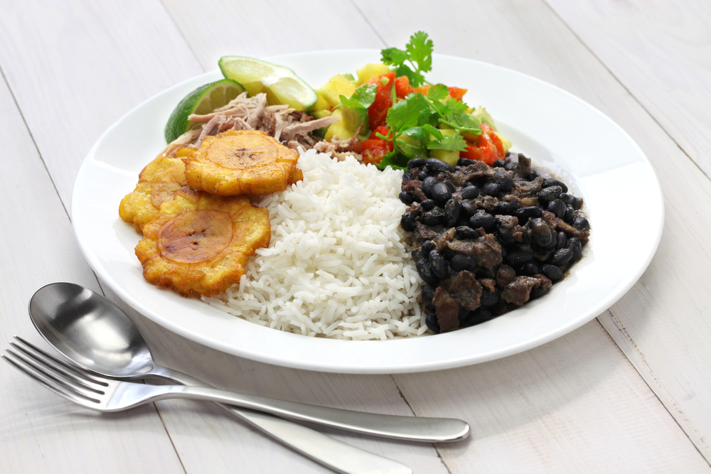 A plate of rice, black beans, fried plantains, and fresh salsa one of the best black owned restaurants in New Orleans