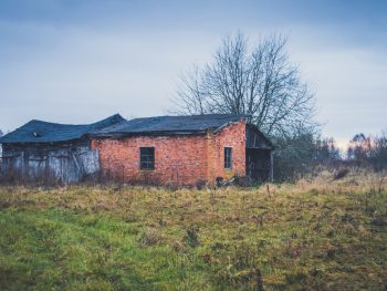 Photo of an abandoned brick home in the middle of an empty field in Alabama