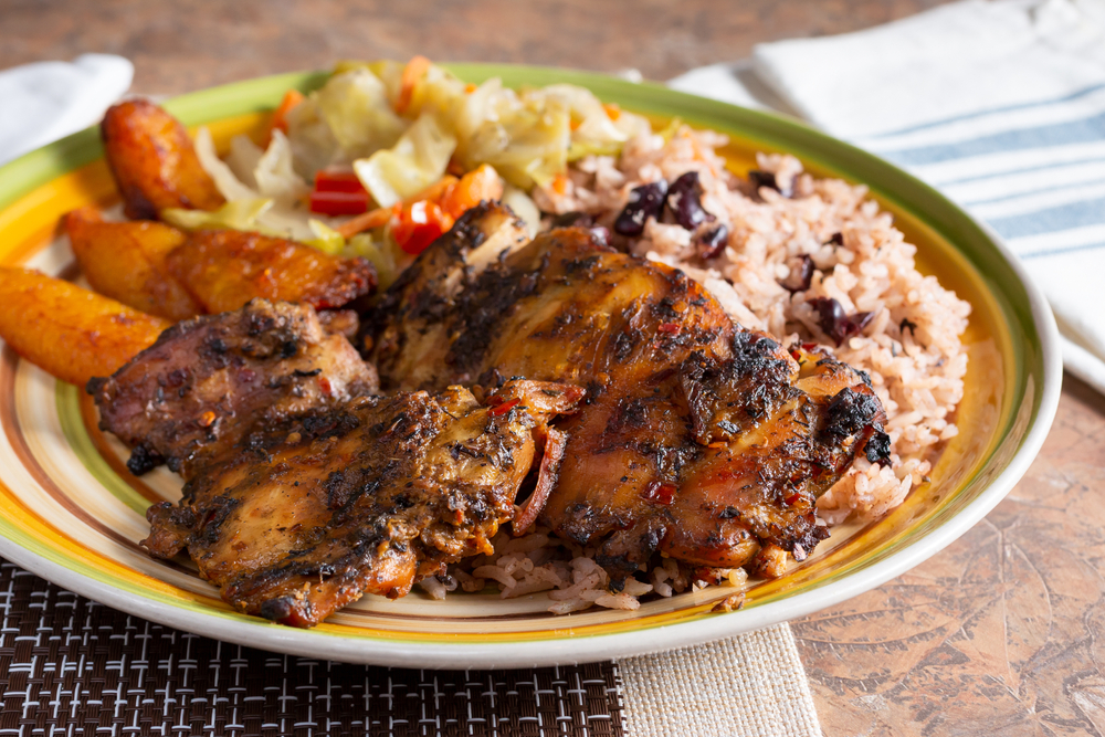 A plate of jerk chicken with black beans and rice and other sides at one of the best black-owned restaurants in new orleans
