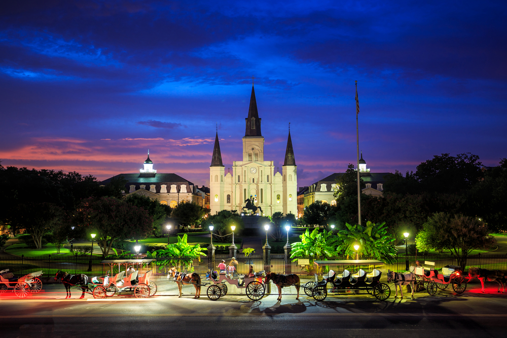 A photo of Saint Louis Cathedral and Jackson Square with horse drawn carriages at sunset.