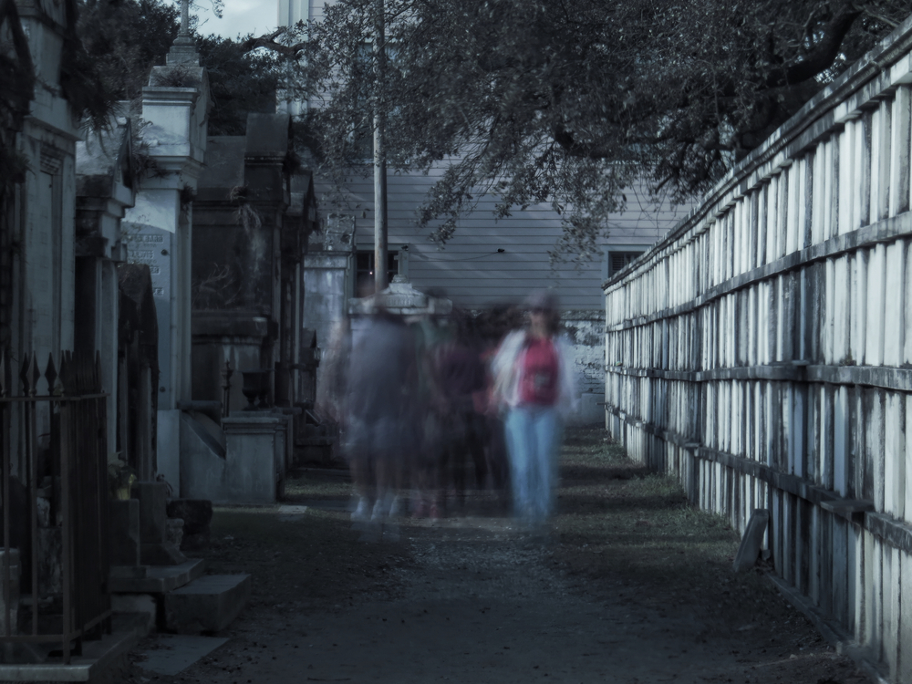 A walking ghost tour exploring a New Orleans cemetery at night.