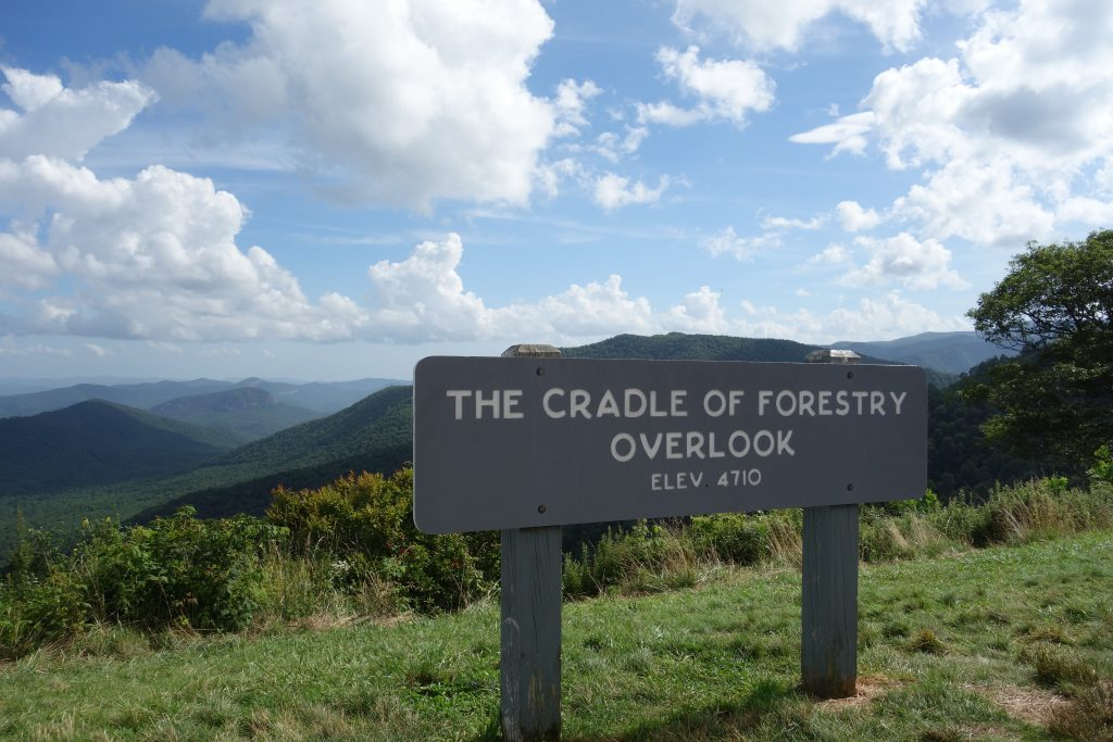 A sign shows the cradle of forestry overlook, showing the hills and mountains of North Carolina.