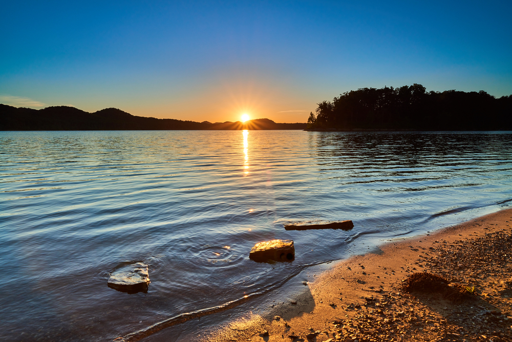 A photo of the sun setting on the horizon of a Kentucky beach.