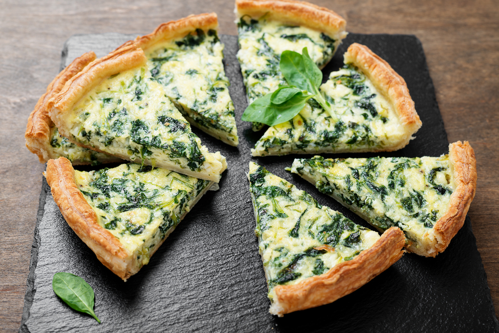 A plate of spinach quiche on a black slab