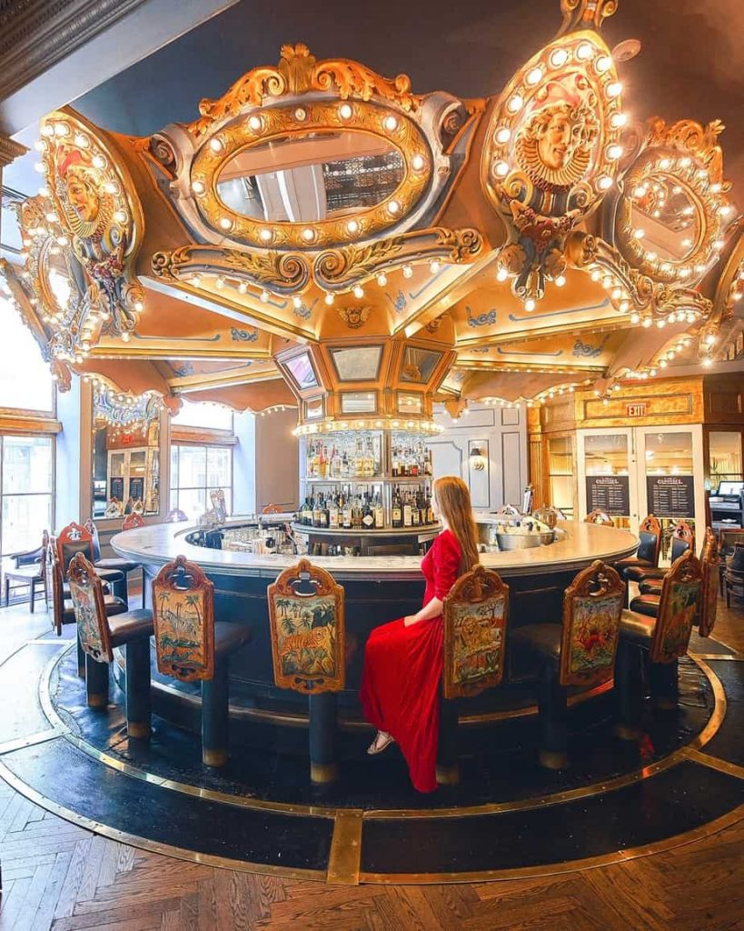 A woman sitting at a bar that is a carousel in New Orleans