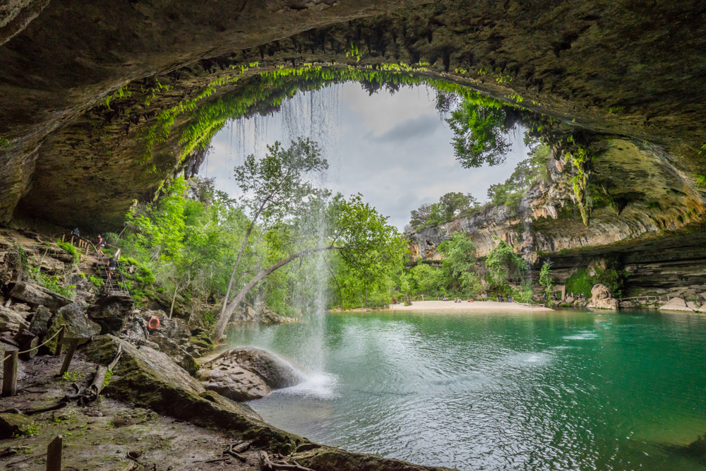 The scenic view of a small waterfall cascading over the mouth of a cave into a grotto filled with aqua water makes Dripping Springs one of the most refreshing waterfalls in texas