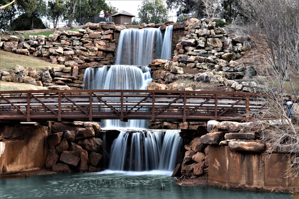 Wichita Falls a three layered waterfall surrounded by rocks with a bridge in front one of the best waterfalls in texas