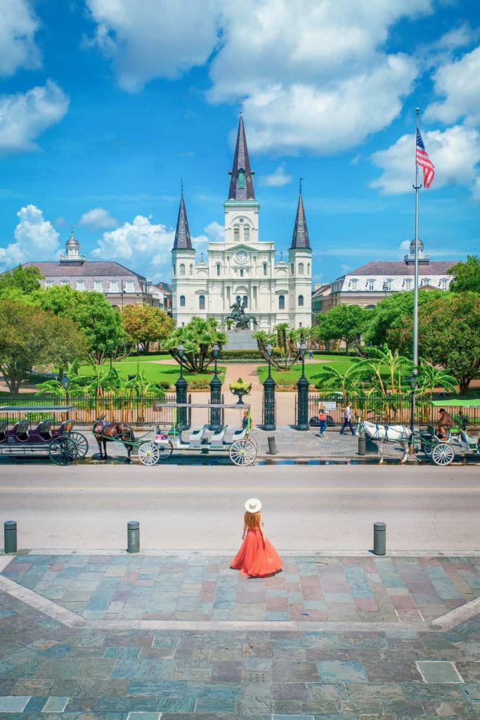 A woman in a long coral dress and sunhat standing in Jackson Square New Orleans