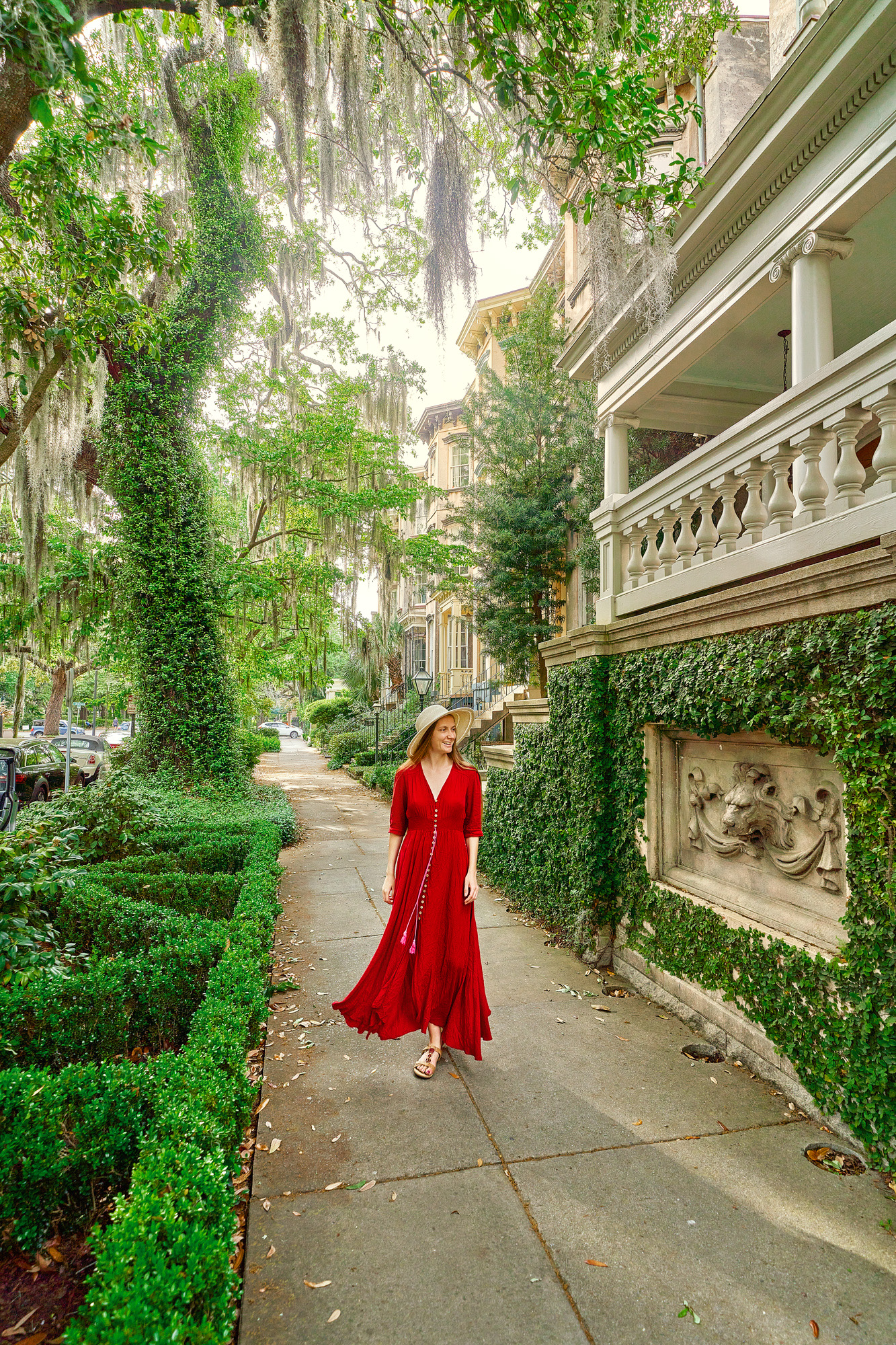 A woman in a red dress standing on the sidewalk of a beautiful street in Savannah. One side of the sidewalk is lined with historic homes covered in ivy and other greenery. The other side has trees and boxwood shrubs