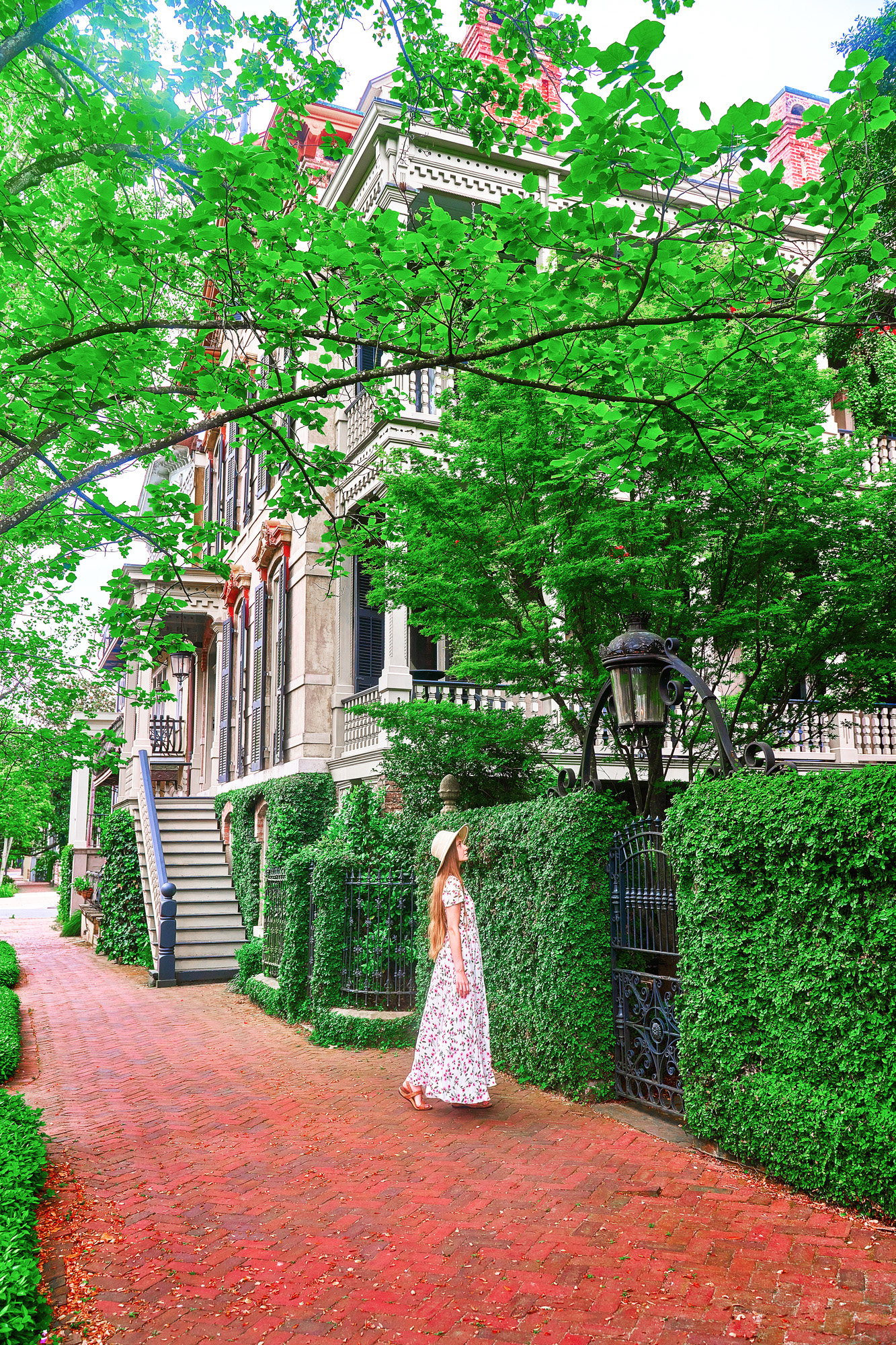 A woman in a white floral maxi dress, with long hair, wearing a white sunhat standing on a brick cobblestone sidewalk. She is looking up at a building that is out of the frame. Standing in front of a wrought iron gate covered in ivy. In the background you can see several historic homes down the street.