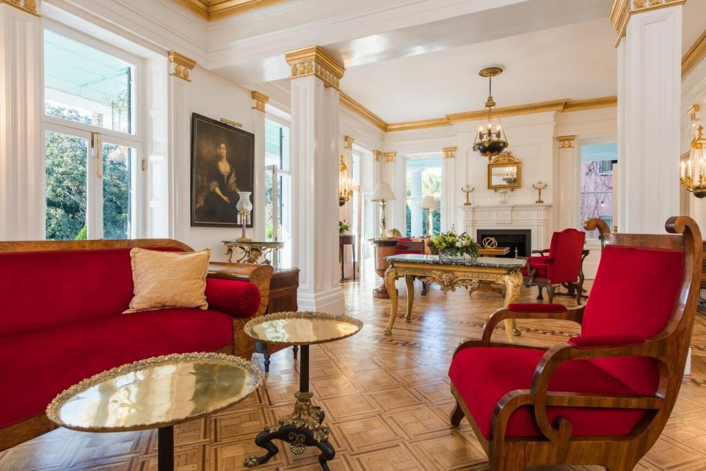 The lobby of an ornately decorated bed and breakfast. There are white walls, gold trim, ruby red furnishings, and gold tables and chandeliers. There are windows on every wall.