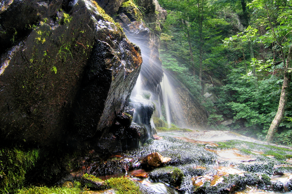 A photo of water spraying from the bottom of a waterfall on Apple Orchard Falls Trail, one of the best Blue Ridge Parkway hikes.