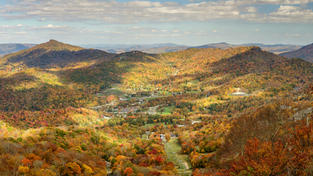 A picture of hills and mountains covered in a sea of trees turning orange and yellow in the fall in Banner Elk.
