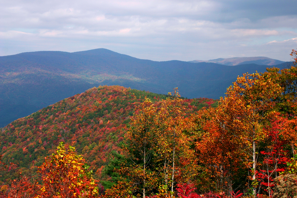 Photo from Fort Mountain where you can see a mountain range covered in bright hues of orange, green, and red.
