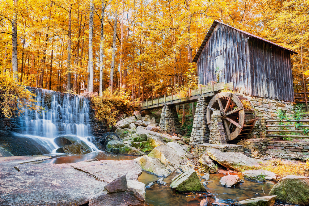 Photo of an old mill near Marietta standing beside a small cascading waterfall during Fall in Georgia.