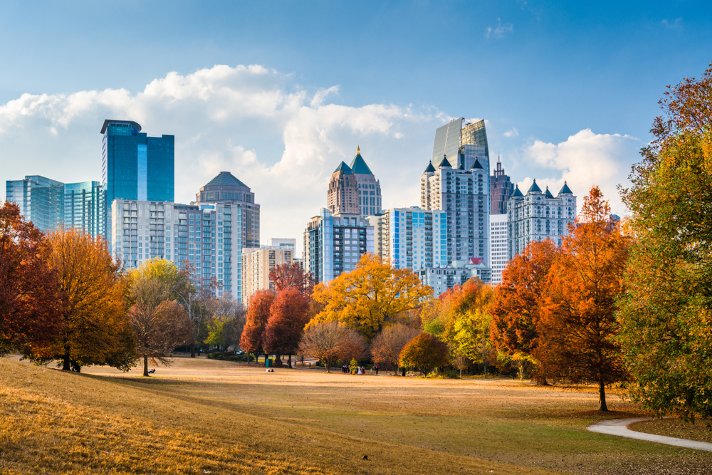 Photo in a field in Piedmont Park where the skyline of Atlanta, Georgia can be seen above a colorful hedge of various trees during Fall in Georgia.