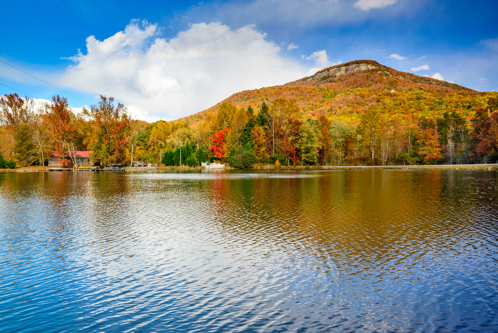 Photo looking across a lake where you can see Yonah Mountain covered in Georgia fall foliage of deep oranges and reds.