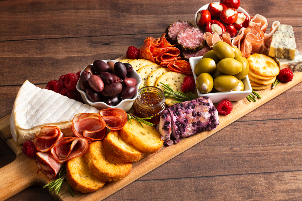 A charcuterie board loaded with cheeses, olives, meats, crackers, and  crostini. Restaurants in San Antonio like Bliss offer such delights