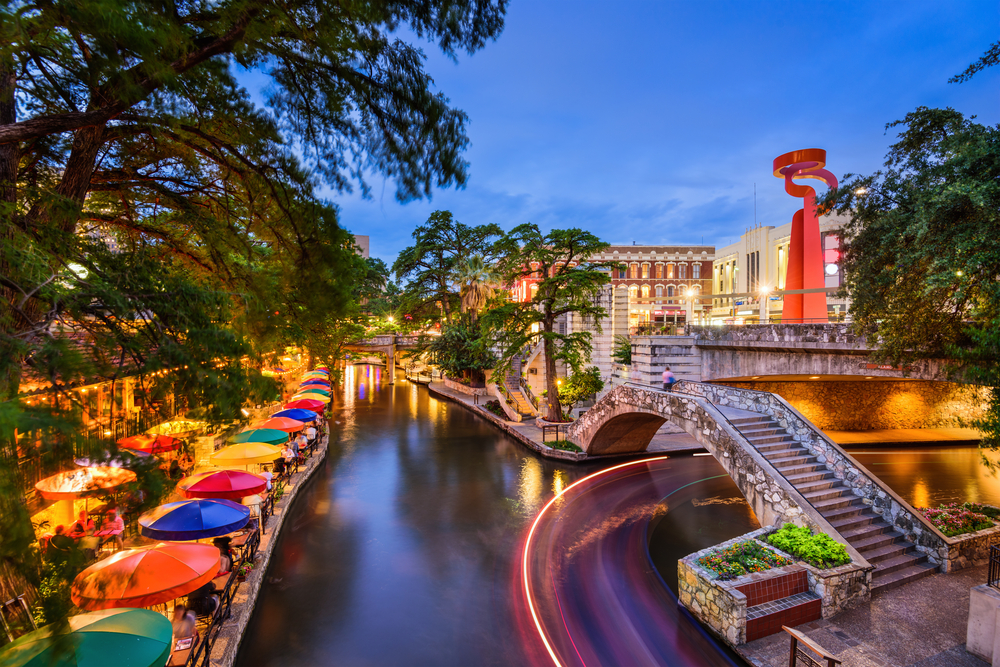 An evening photo of the Riverwalk in San Antonio. Tables with brightly colored umbrellas line the edge of the river.