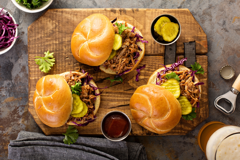 A cutting board holding three pulled pork sandwiches with pickles and bbq sauce. Get one just like it at the Big Bib BBQ, a black-owned restaurant in San Antonio