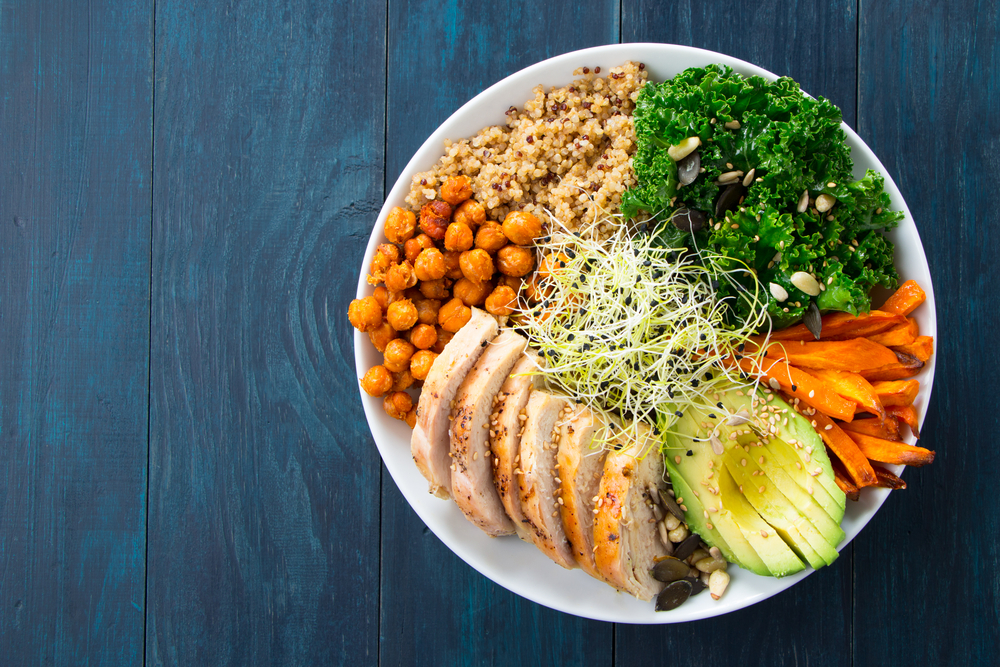 A Buddha bowl with ingredients like chickpeas, kale, carrots, and quinoa