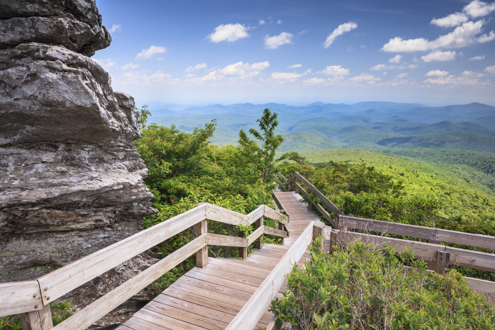 A photo of an overlook with a view of mountains on the Tanawha Trail, one of the most scenic Blue Ridge Parkway hikes.