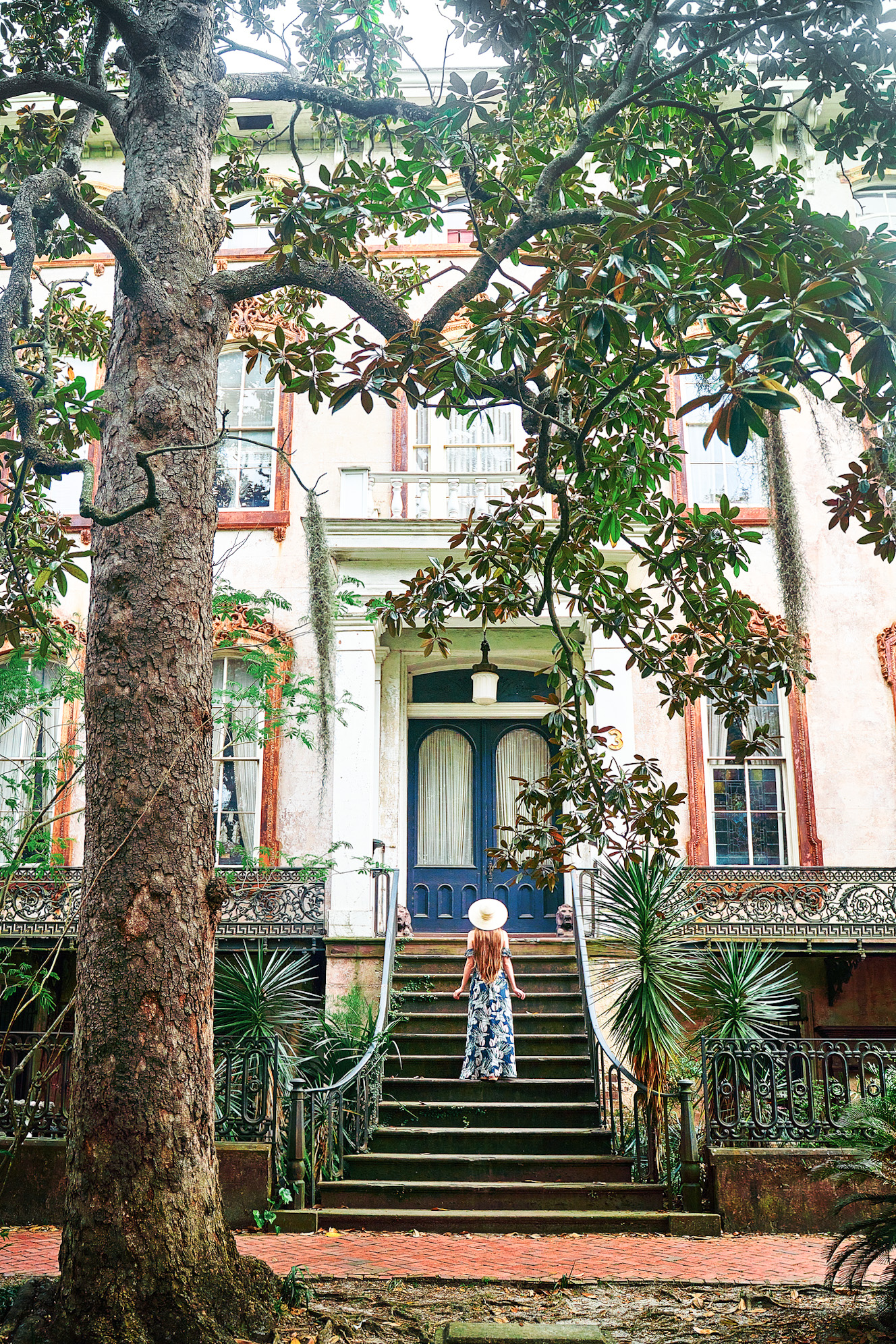 Photo of a girl standing on the steps of a house in Savannah's Historic District, one of the best neighborhoods to stay in Savannah!